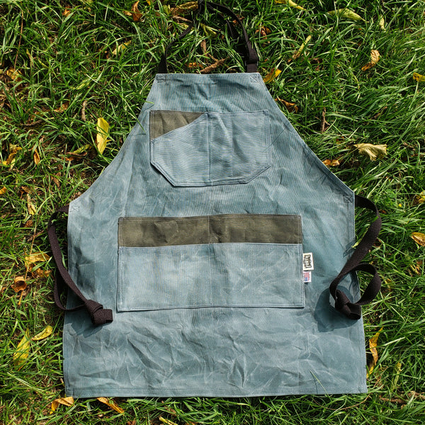 Blue and grey apron with black straps. Hand Waxed and laying in the grass.