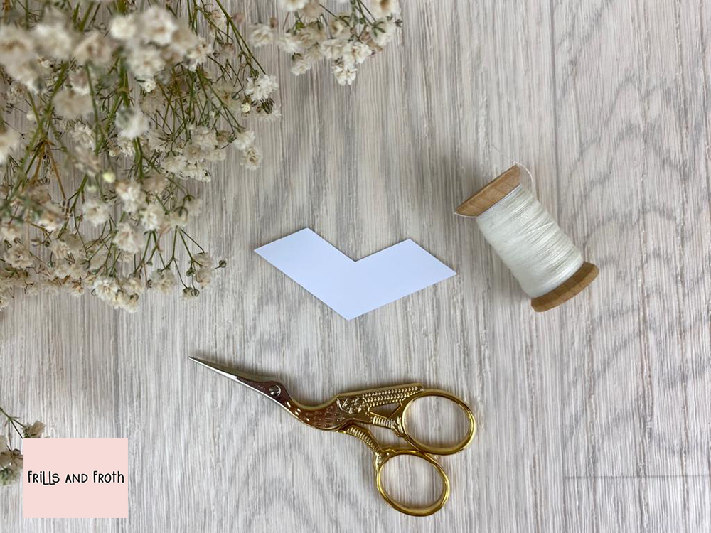 Picture of single Arrow EPP card paper piece, surrounded by sewing notions and flowers, English Paper Piecing Arrow Papers  Our Arrow English paper piecing (or EPP for short) papers are made out of thin flexible card, mechanically cut in house for accuracy.