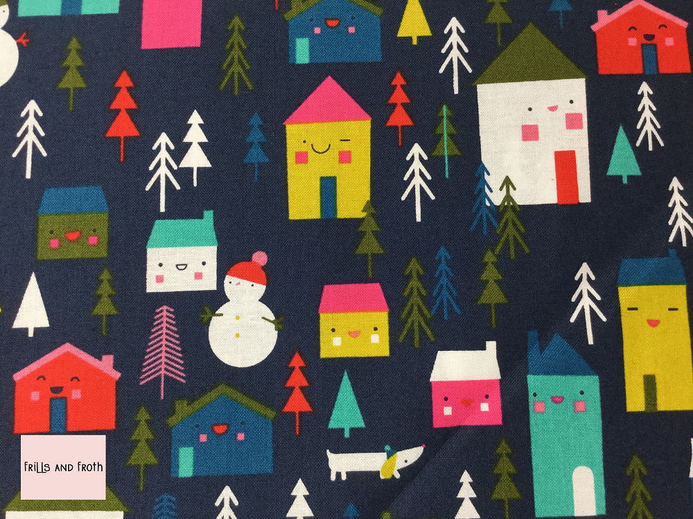 Dashwood Studio 'Merry and Bright' Houses and Dogs quilting fabric Dashwood Studio 'Houses and Dogs' from the Merry & Bright collection features houses with cute faces in various sizes along with dogs trees and snowmen in a variety of colours and sizes on a blue background.