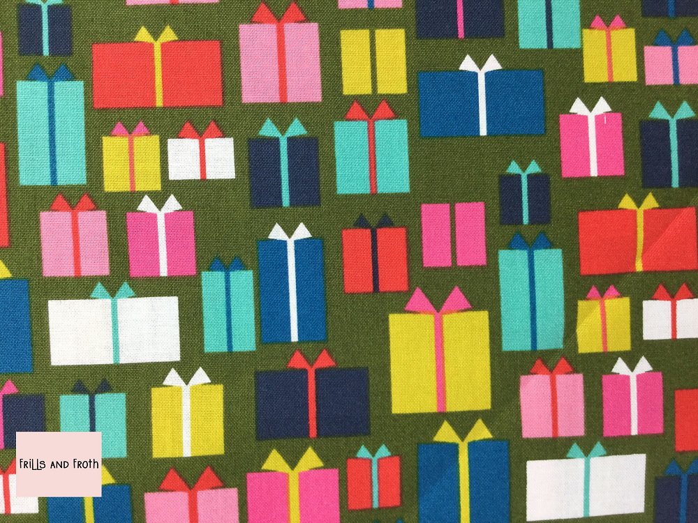 Dashwood Studio 'Merry and Bright' Presents quilting fabric Dashwood Studio 'Presents' from the Merry & Bright collection features wrapped gifts in various sizes in a variety of colours on a green background.