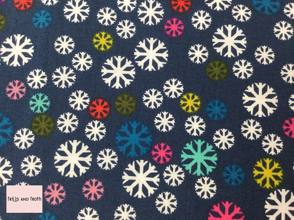 Dashwood Studio 'Merry and Bright' Snowflake quilting fabric Dashwood Studio 'Snowflake' from the Merry & Bright collection features snowflakes in various sizes in a variety of colours on a blue background.