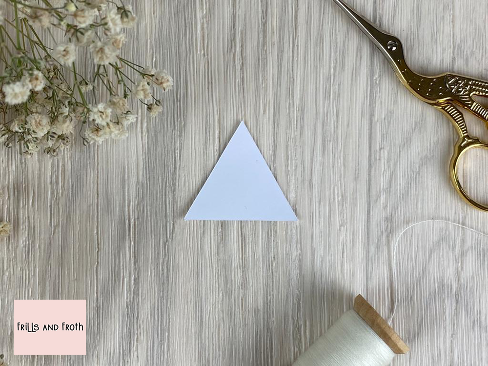 Picture of EPP Equilateral Triangle Paper shape surrounded by sewing notions and flowers. English Paper Piecing Equilateral Triangle Papers  Our Equilateral Triangle English paper piecing (or EPP for short) papers are made out of thin flexible card, mechanically cut in house for accuracy.