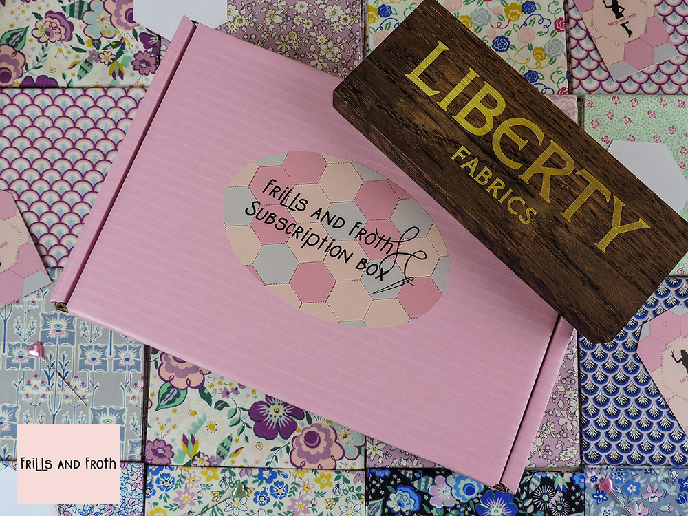 Picture of Liberty Feast of EPP box laid on Liberty fabric along with wooden Liberty sign.