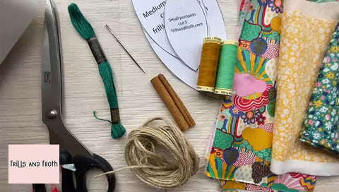 Image shows sewing equipment and fabric used to make a sewn pumpkin