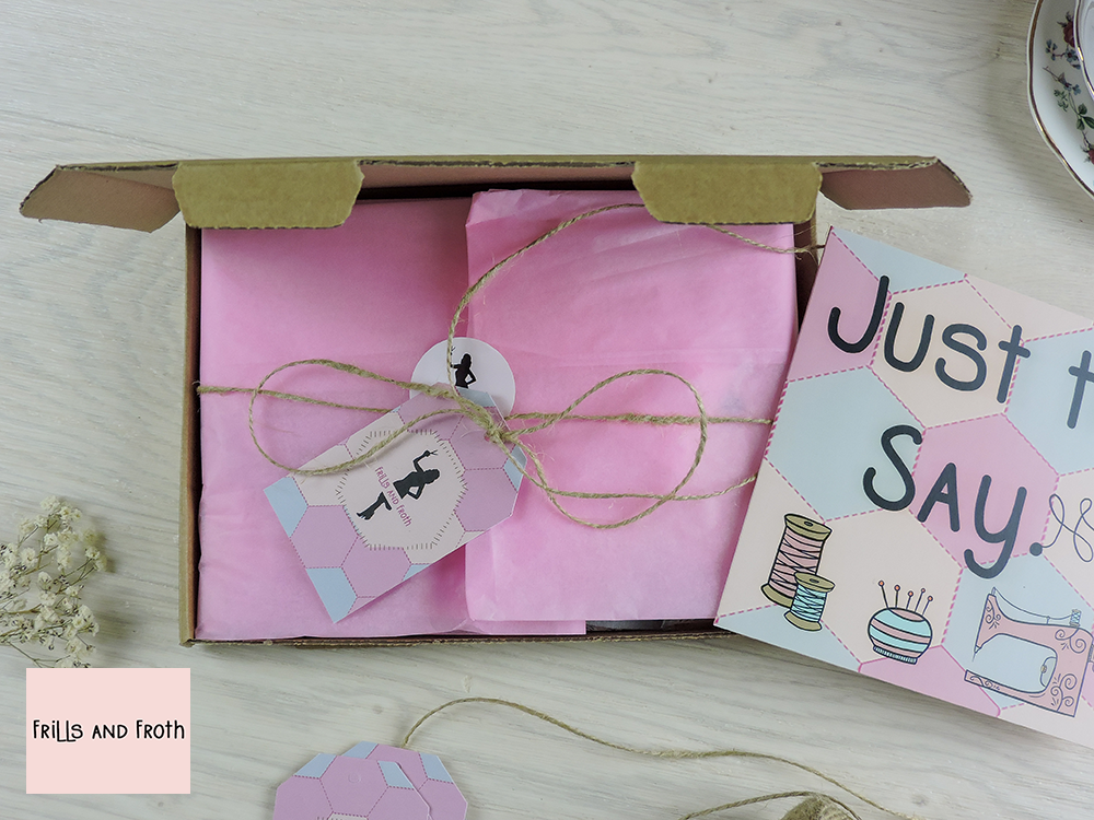 """Picture showing open gift box wrapped with tissue tied with string and tag along with a gift card saying """"Just to say"""". surrounded by flowers, string and a teacup and saucer."""