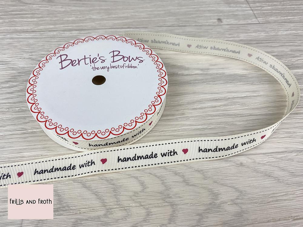 Picture of Handmade with love ribbon. 16mm Grosgrain ribbon. Bertie's Bows Handmade with love ribbon. This 3 metre reel of beautiful ribbon has a continuous repeat of, 'Handmade with ❤'. An ideal addition to any hand sew project as either intended for a gift or just as a reminder to yourself.