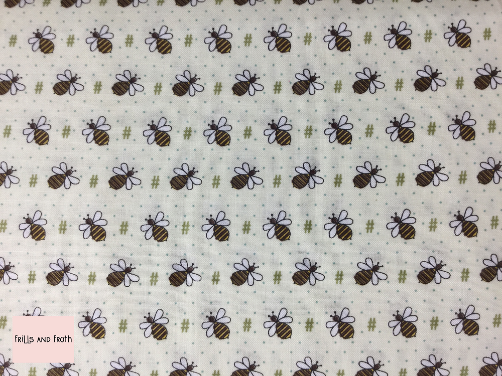 Henry Glass 'All About The Bees' 'Bee Hash Tag' quilting fabric This quilting fabric from the 'All About the Bees' collection by Henry Glass features bees and Hash Tag symbols on a cream background.