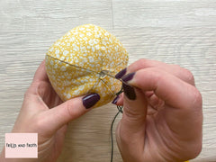 Sewing with jute string or embroidery floss on our pumpkin made from Liberty fabric.