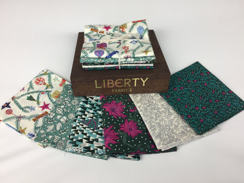 Liberty Fabric 'Seasons Greetings' Fabric Fat Quarter Bundle in pink and green. This bundle has six iconic fabric fat quarters from the Liberty 'Seasons Greetings' collection in pink and green. sold by UK Liberty of London fabric stockist Frills and Froth. seller of designer fabric from Liberty