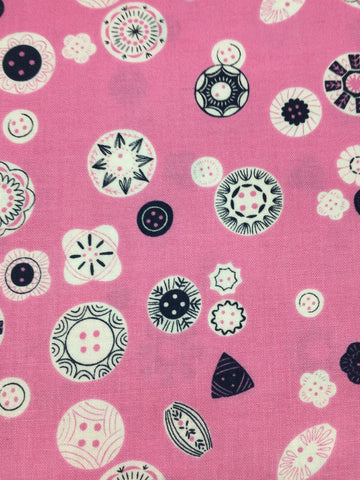 Dashwood Studio 'Button' fabric. A 100% cotton quilting weight fabric. This fabric from Dashwood Studio features buttons in various sizes in black and white on a pink background. This fabric is suitable for dressmaking, quilting and home decor.   100% cotton fabric 112 cm wide Medium weight. Sold by the half metre and metre. sold by UK Liberty of London fabric stockist Frills and Froth. seller of designer fabric from Dashwood Studio