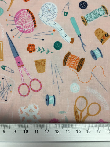 Dashwood Studio 'Sewing Notions' fabric. A 100% cotton quilting weight fabric. This fabric from Dashwood Studio features scissors, thimbles pins and all manner of notions in orange, aqua and white all on a pink background. This fabric is suitable for dressmaking, quilting and home decor.   100% cotton fabric 112 cm wide Medium weight. Sold by the half metre and metre. sold by UK Liberty of London fabric stockist Frills and Froth. seller of designer fabric from Dashwood Studio