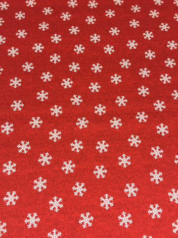 Studio E 'Snowflake' fabric. A 100% cotton quilting weight fabric. This fabric from Studio E fabrics features a white snowflake design on a red background. sold by Studio E fabrics fabric stockist Frills and Froth. seller of designer fabric from Studio E fabrics