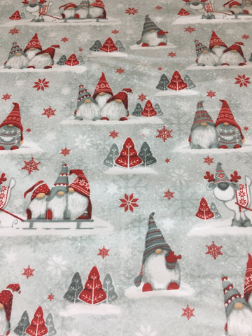 Henry Glass 'Winter Wimsey' brushed cotton fabric. A 100% brushed cotton quilting weight Christmas fabric. This beautiful fabric features playful gnomes and reindeer's in red and grey surrounded by tree's and snowflakes a blue background.sold by Henry Glass fabric stockist Frills and Froth. seller of designer fabric from Henry Glass
