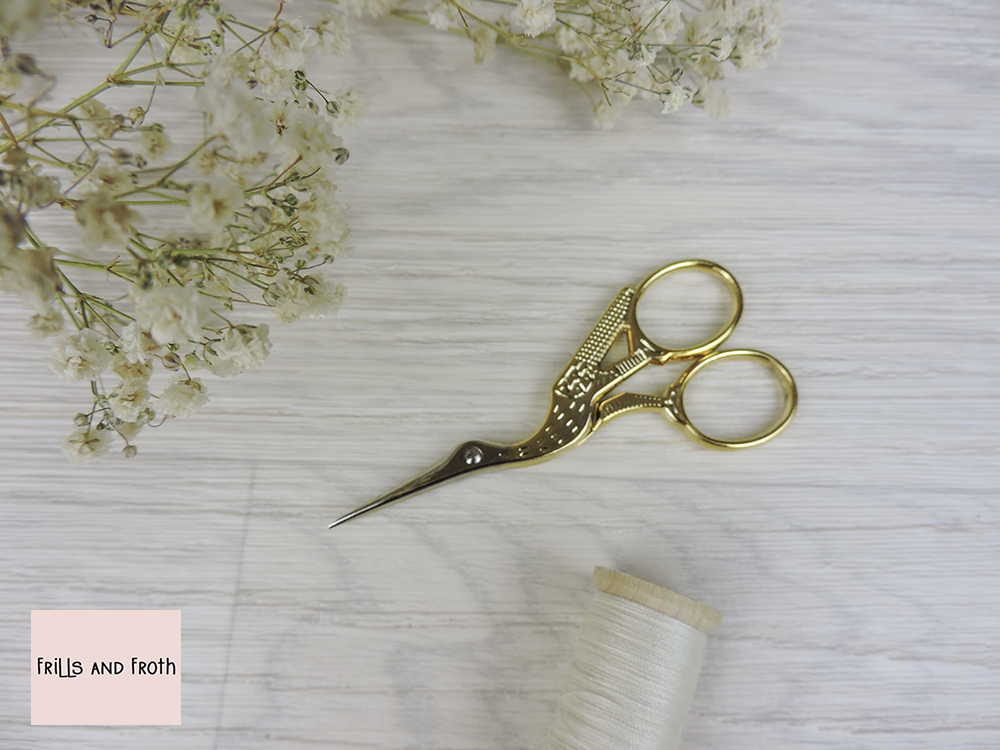 """Janome 'Stork' Embroidery Scissors 3.5"""" (9cm) Brass embossed embroidery scissors from Janome. Delicate embroidery scissors, handy for sewing on the go. Shaped for comfort and just the right size to slip into your sewing kit. Come complete with a handy pouch so keep them looking their best."""