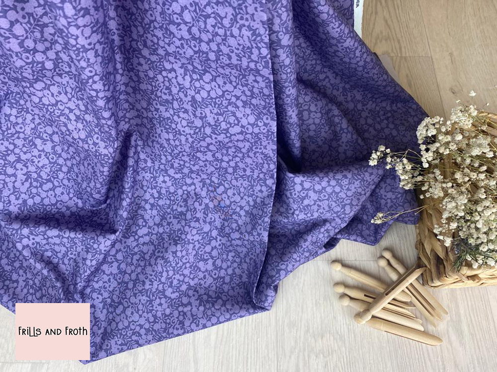 Picture showing drape of this Liberty Fabric along with wooden pegs and a basket of flowers.Liberty fabric 'Wiltshire Shadow' Lavender quilting fabric Liberty 'Wiltshire Shadow' fabric from the Liberty blender collection features a tone on tone floral design.
