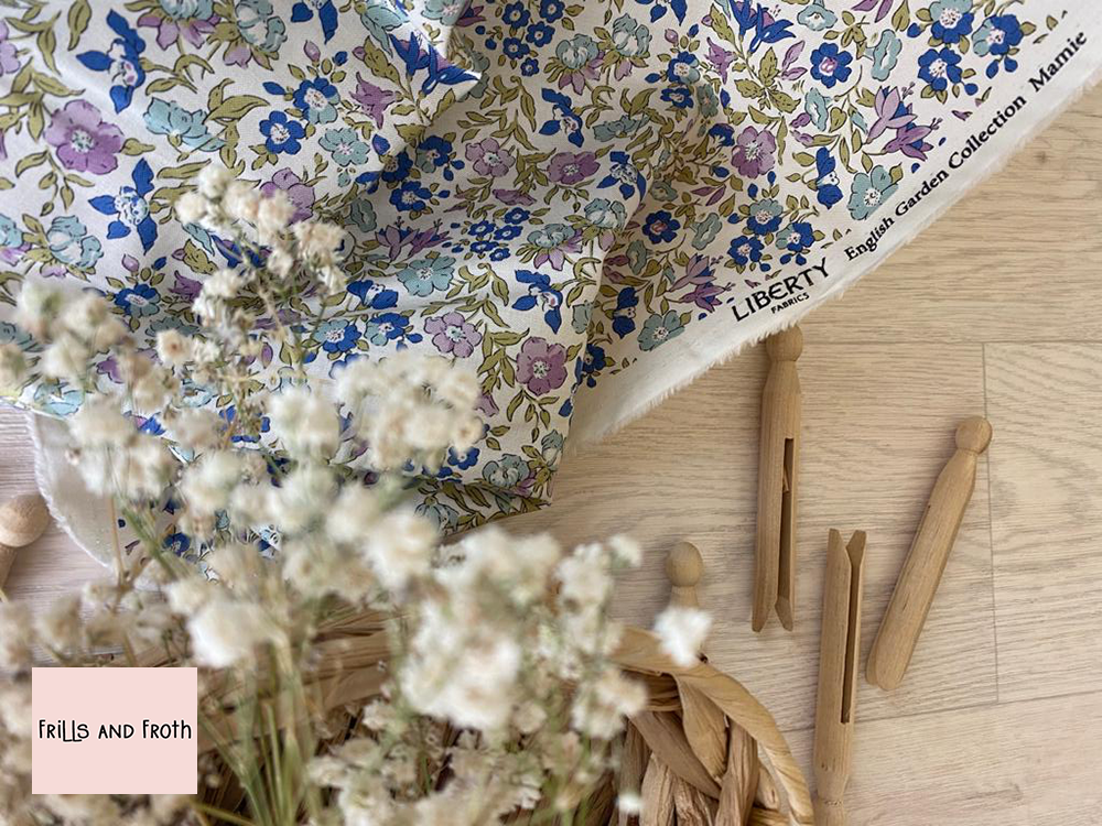 Picture showing drape of this Liberty Fabric along with wooden pegs and a basket of flowers. Liberty fabric 'Mamie' quilting fabric Liberty 'Mamie' fabric from the 'English Garden' collection features a multi coloured floral design.