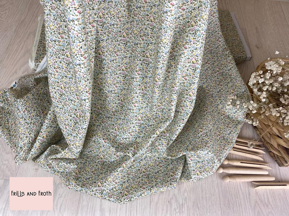Picture showing drape of this Liberty Fabric along with wooden pegs and a basket of flowers. Liberty fabric 'Newland Large' quilting fabric Liberty 'Newland Large' fabric from the 'English Garden' collection features a multi coloured floral design.