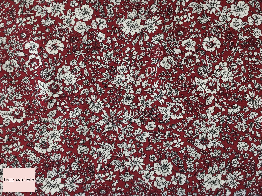 Liberty fabric 'Emily Silhouette Flower' quilting fabric Liberty 'Emily Silhouette Flower' fabric from the 'Flower Show Winter' collection features a white floral design on a red background.