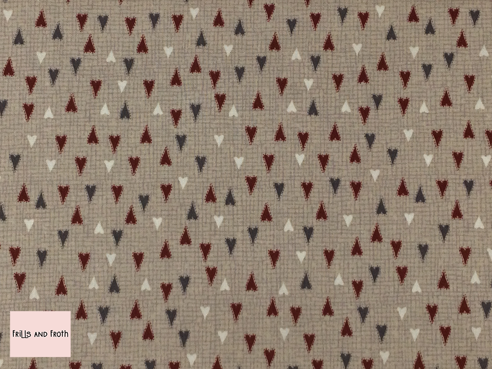Lynette Anderson fabric 'Hearts' quilting fabric in taupe. Lynette Anderson fabric 'Hearts' quilting fabric from the 'Scandinavian Christmas 2' collection features red, white and neutral heart's on a taupe fabric.