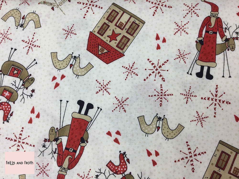 Lynette Anderson fabric 'Santa' quilting fabric. Lynette Anderson fabric 'Santa' quilting fabric from the 'Scandinavian Christmas 2' collection features Santa, reindeer, birds and houses on a white fabric adorned with stars and hearts.