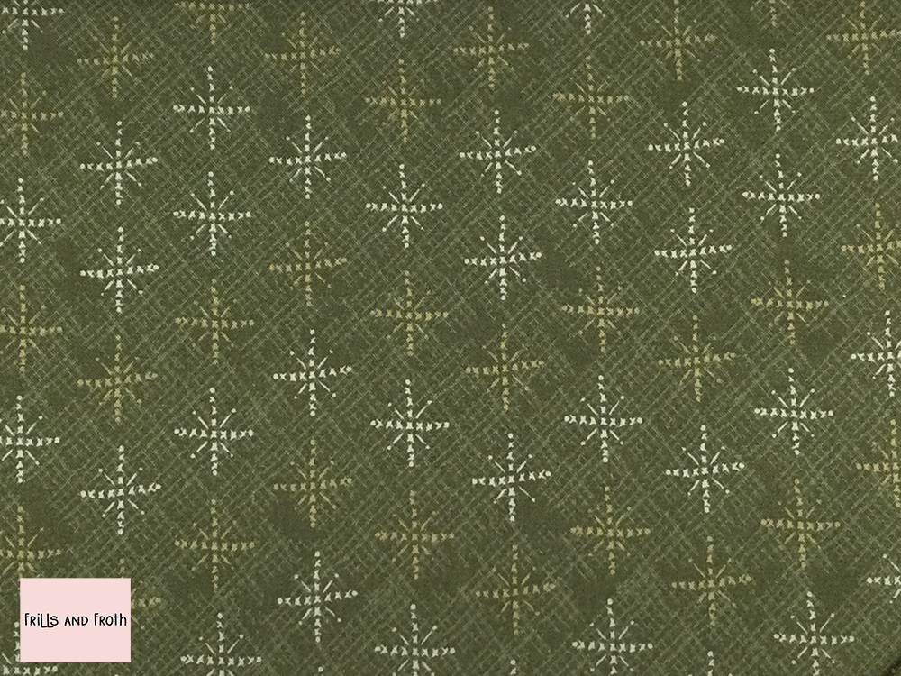 Lynette Anderson fabric 'Snowflakes' quilting fabric in green. Lynette Anderson fabric 'Snowflakes' quilting fabric from the 'Scandinavian Christmas 2' collection features snowflakes on a green fabric.