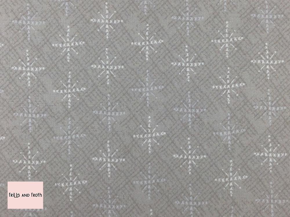 Lynette Anderson fabric 'Snowflakes' quilting fabric. Lynette Anderson fabric 'Snowflakes' quilting fabric from the 'Scandinavian Christmas 2' collection features white snowflakes on a neutral fabric.