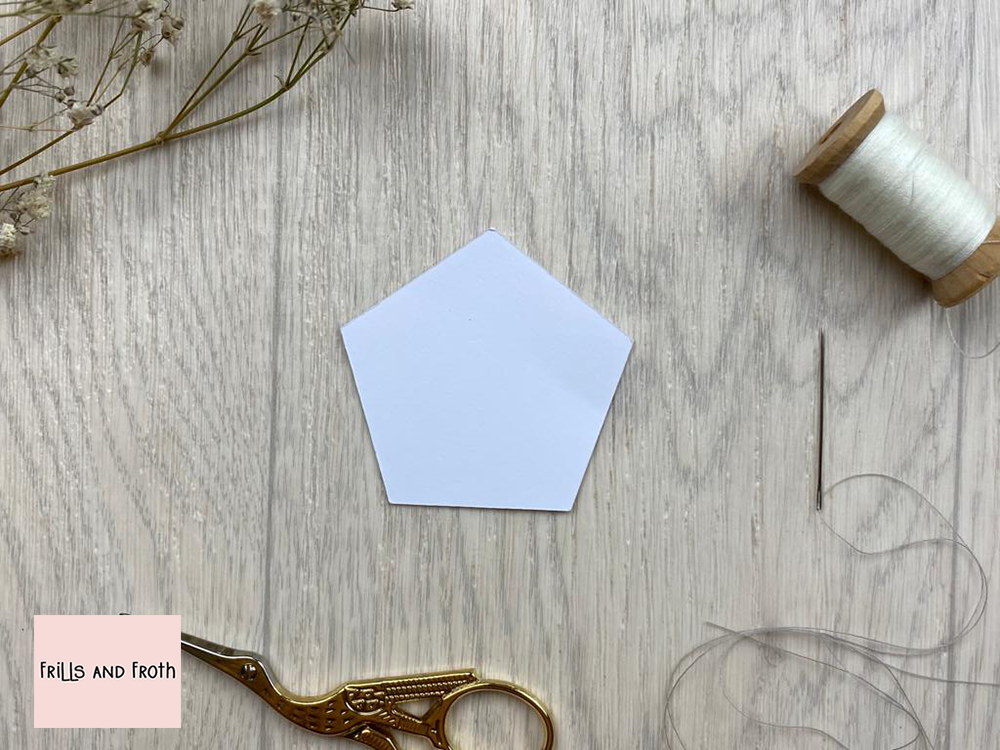 Picture of single Pentagon EPP paper shape, surrounded by sewing notions and flowers. English Paper Piecing Pentagon Papers  Our Pentagon English paper piecing (or EPP for short) papers are made out of thin flexible card, mechanically cut in house for accuracy.