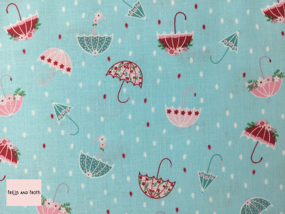 Riley Blake 'Singing in the Rain' 'Umbrella's' in Waterfall blue quilting fabric This quilting fabric from the 'Singing in the Rain' collection by Riley Blake features a red, pin and blue umbrella print on a white background.