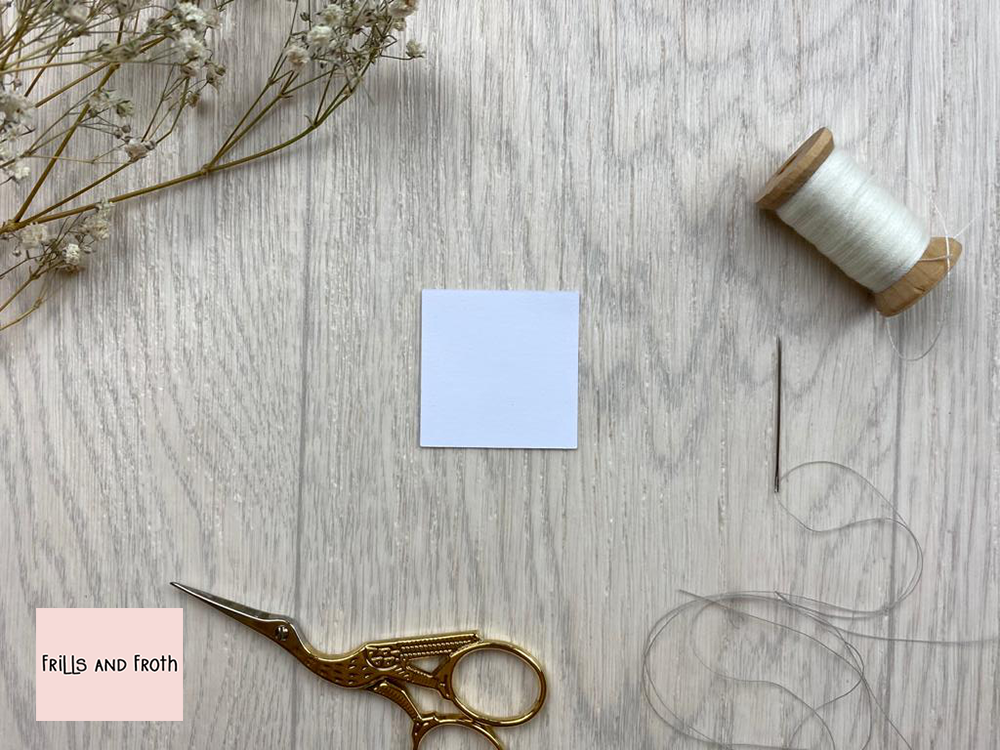 Picture of single Square EPP paper shape, surrounded by sewing notions and flowers. English Paper Piecing Square Papers  Our Square English paper piecing (or EPP for short) papers are made out of thin flexible card, mechanically cut in house for accuracy.