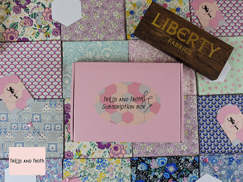 Picture showing our Liberty taste of Hexies subscription box laid on a patchwork of Liberty fabric along with a wooden Liberty sign.