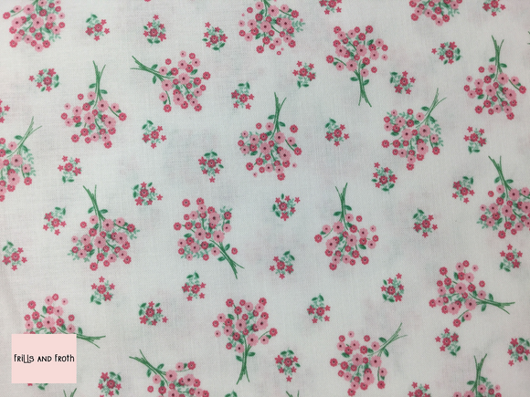Riley Blake 'Singing in the Rain' 'Bouquet's' in White quilting fabric This quilting fabric from the 'Singing in the Rain' collection by Riley Blake features a floral print on a white background.