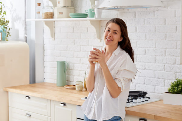 Woman drinking clean water next to her sink