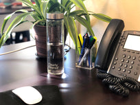 Glass water bottle at work desk