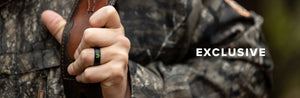 Exclusive, man holding a gun strap while dressed in camo wearing a bone collector ring