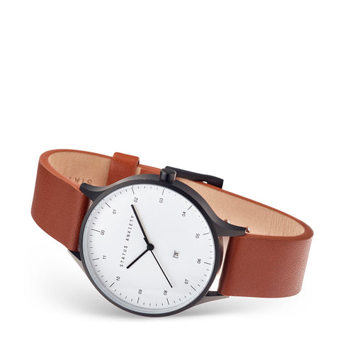products/status-anxiety-watch-inertia-matte-black-white-face-tan-strap-front-angle.jpg