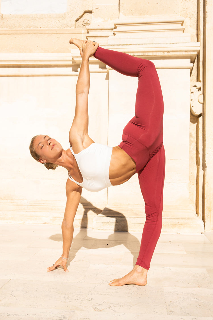 Alice Maisetti wears a white yoga bra and root chakra red legging by von Mandala