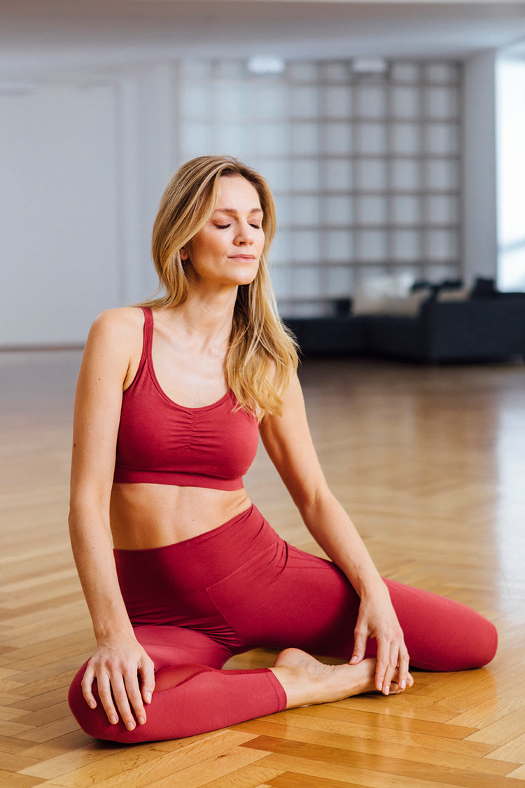 Yogini wears a root chakra red yoga bra and legging by Mandala