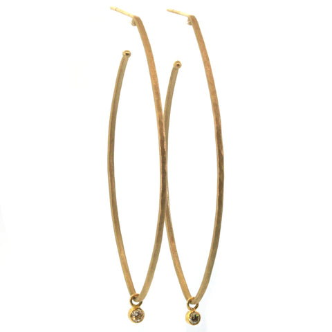 These Elongated Diamond Dangle Hoops from Rebecca Lankford Designs are fit for a queen. Each hoop features a glistening white diamond bezel set and dangling from a textured, yellow gold oval hoop.
