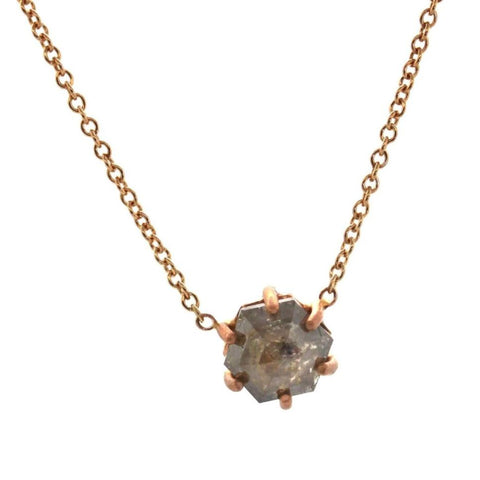 hexagon shaped raw diamond in a rose gold prong setting on a rose gold chain