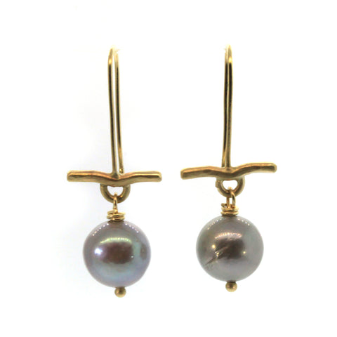These Pearl & Gold Bar Earrings were handcrafted in Houston, Texas at Rebecca Lankford Designs. This pair features two round grey pearls accented by a textured yellow gold bar dangling from yellow gold ear wire.