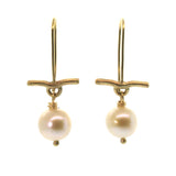 These Pearl & Gold Bar Earrings were handcrafted in Houston, Texas at Rebecca Lankford Designs. This pair features two round cream pearls accented by a textured yellow gold bar dangling from yellow gold ear wire.