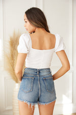 Back view of white puff sleeve crop top with zipper closure.