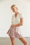 Pink plaid mini skirt with a pleated design.