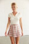 pink plaid skirt with a white ribbed polo top.