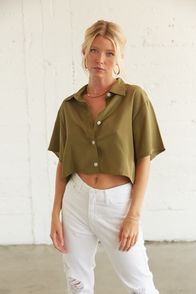 This boxy cropped shirt features a button up front and short sleeves.