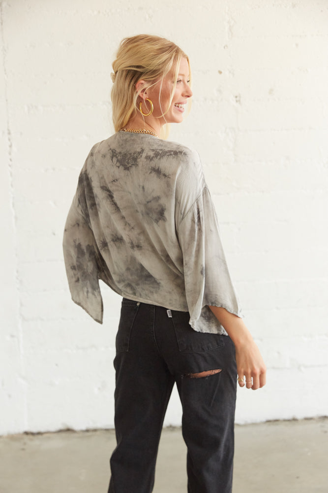 The back of this crop top is simple with a grey tie dye design and flowy kimono sleeves.