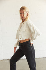 Side of white cropped denim jacket, complete with a raw distressed hem.