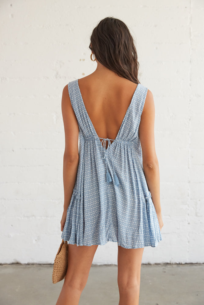 The back of this dress features a tassel tie detail and an open V back.