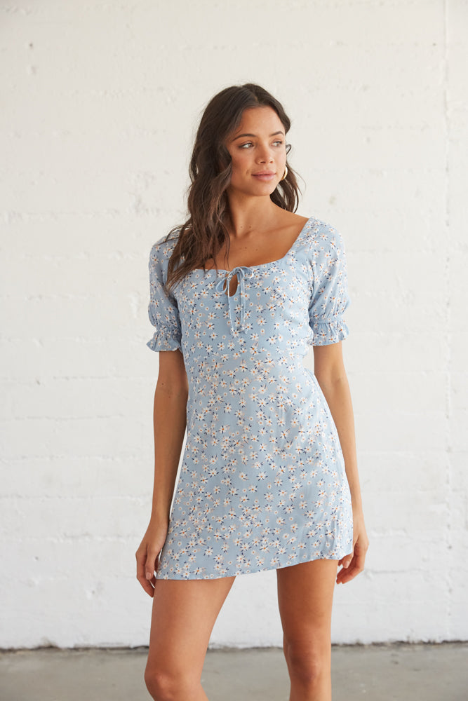Blue floral mini dress with a front tie detail.