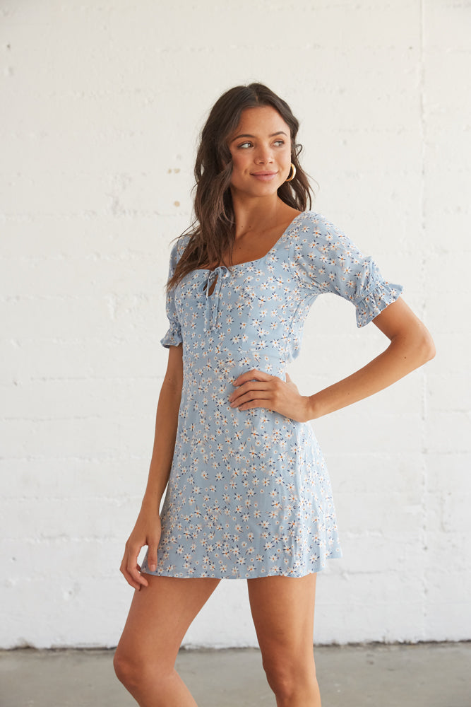 Dreamy blu emini dress with puffy short sleeves, a relaxed silhouette, and a front tie detail.